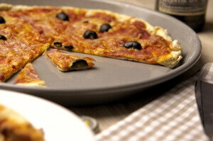 Biertreber-Pizza mit Bacon mit schwarzen Oliven