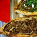 türkische Pide mit Hackfleischfüllung, Rucola und Fetakäse aus dem Ofen