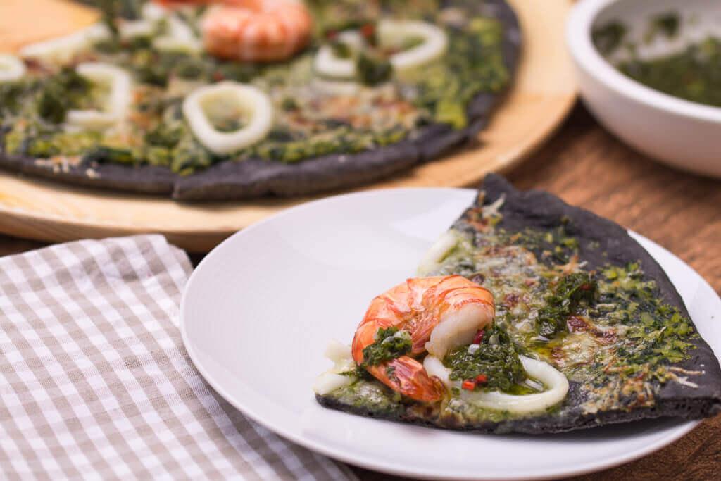 Schwarze Pizza mit Tintenfisch und Garnelen