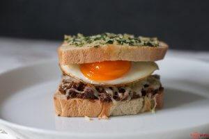 Sloppy Joe Sandwich mit Käse überbacken und Spiegelei