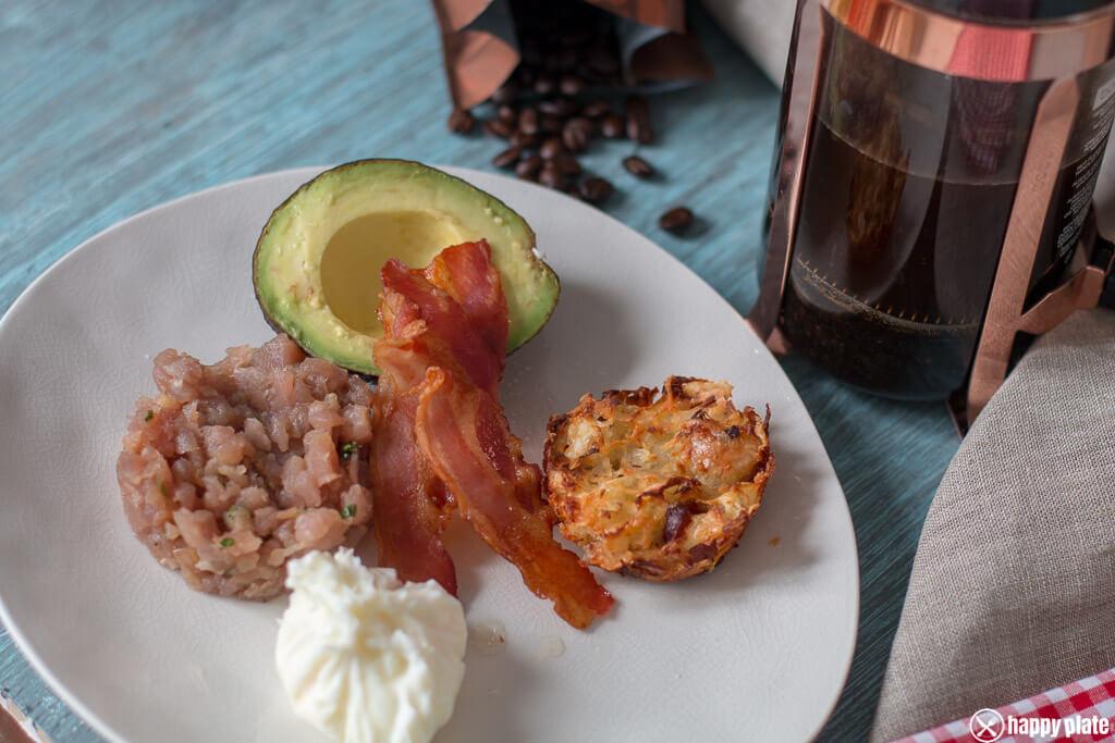 Hash Browns Muffins 0,4 kg Kartoffeln, mehlig kochend 4 Scheiben Bacon 1 Schalotte 1 Teelöffel Olivenöl 150 g Emmentaler, gerieben 1 Teelöffel Petersilie Salz, Pfeffer Tunfischtatar 400 g Tunfisch, frisch 3-4 Stile Koriander 1 Schalotte 1/2 Limette 1 Teelöffel Sesamöl 2 Esslöffel Sojasauce Ausserdem 6 Eier 3 Avocados Ein Spritzer Limette 6 Scheiben Bacon Salz, Pfeffer Hash Browns Muffins Den Backofen auf 180° C vorheizen. Die Kartoffeln schälen und reiben. Danach in ein Sieb geben und unter dem Wasserhahn die Stärke so gut es geht abwaschen. Die Kartoffeln in ein Passiertuch/sauberes Küchentuch geben und auspressen, so dass die Feuchtigkeit bestmöglich rausgeht. Die Zwiebel und den Bacon in kleine Würfel schneiden. Die Kartoffel, das Olivenöl, die Zwiebel, den Bacon, den Käse und die Petersilie miteinander vermengen. Leicht salzen und Pfeffer dazugeben. Eine Muffinform für 6 Muffins leicht einfetten und die Masse in die Form verteilen. Für ca. 30 Minuten im Ofen backen. Tunfischtatar Den Tunfisch mit einem scharfen Messer in kleine Würfel schneiden. Die Schalotte in kleine Würfel schneiden. Den Koriander fein hacken. Alles miteinander vermengen, das Sesamöl, den Saft der halben Limette, so wie den Abrieb und die Sojasauce dazugeben und gut verrühren. Bei Bedarf kurz vor dem Essen salzen. Das Frühstück fertig stellen. Den Bacon in den Ofen bei 180 °C kross werden lassen (Der Ofen sollte von en muffins ja noch warm sein) Einen Topf mit Wasser befüllen, aufkohen und die Herdplatte ausstellen. In der Zwischenzeit ein kleines Stück Folie mit etwas Öl bepinseln,in eine kleine Tasse auslegen udn ein Ei dareingeben. Oben dann richtig zudrehen. Das Ganze mit den anderen 5 Eiern wiederholen. Die Eier für 5-6 Minuten ins Wasser geben. Die Avocado halbieren, und mit etwas Limettensaft und Salz beträufen. Auf dem Teller in die Avocado das pochierte Ei geben und den Bacon zulegen, mit einem Desserting das Tartar anrichten und einen Hash Browns Mufin dazugeben